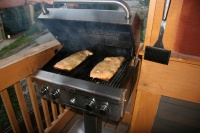 Fresh cedar plank salmon on the gas grill on the balcony.